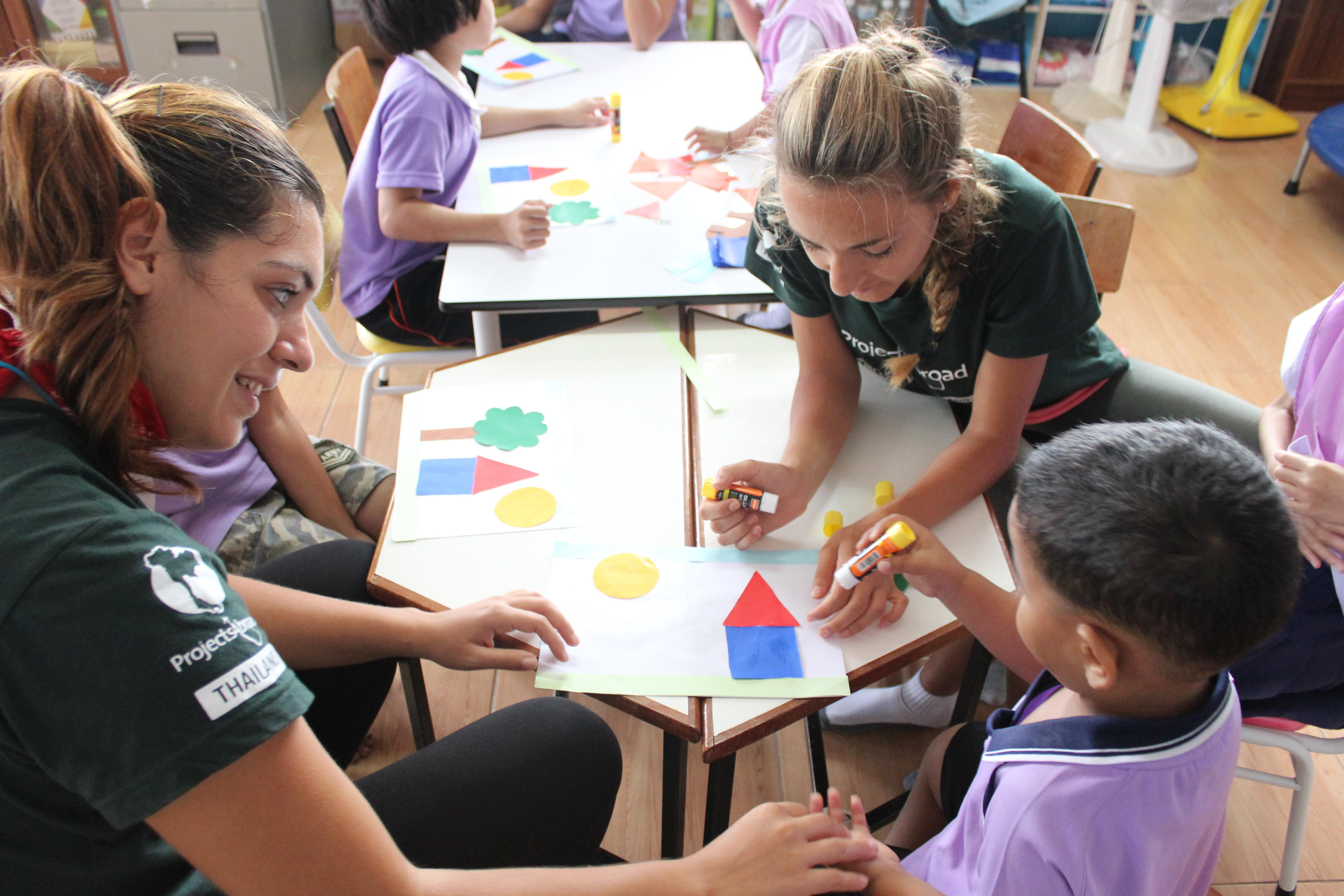 Projects Abroad Childcare volunteers work with children at a daycare centre in Thailand to complete a colouring activity.